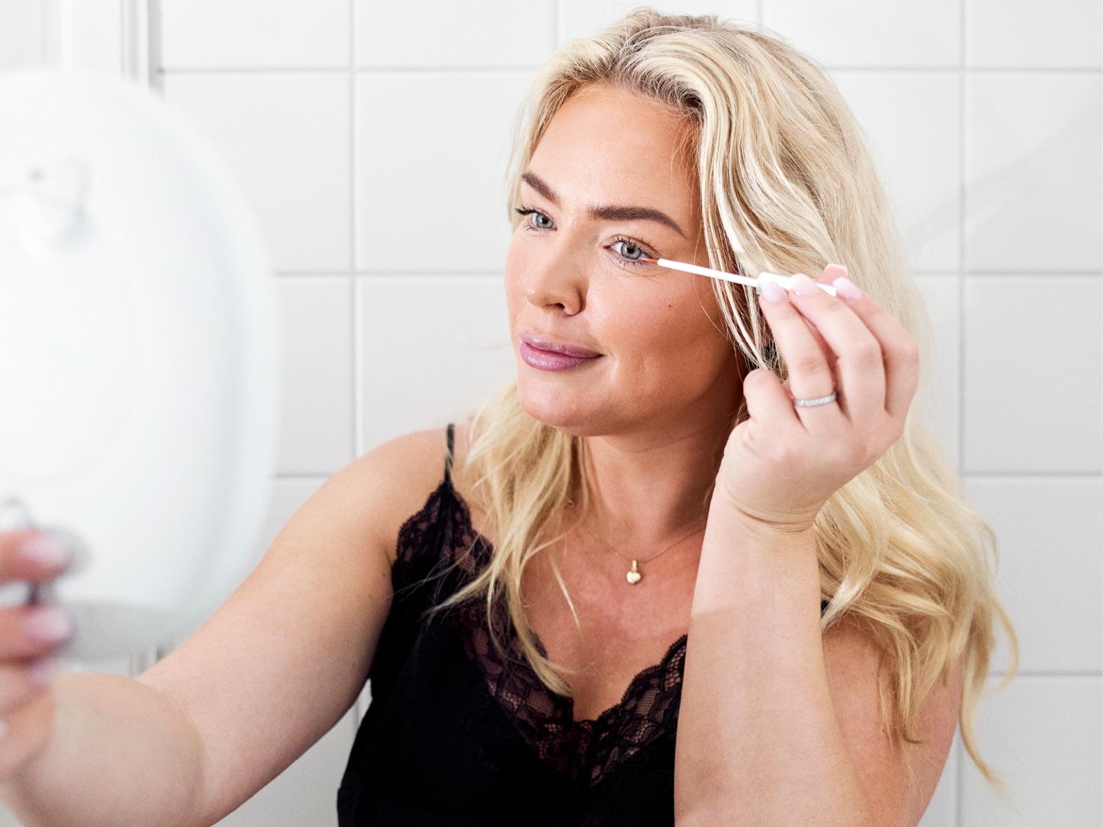 My Martens applying Eyelash Growth Serum from Swiss Clinic in a white bathroom